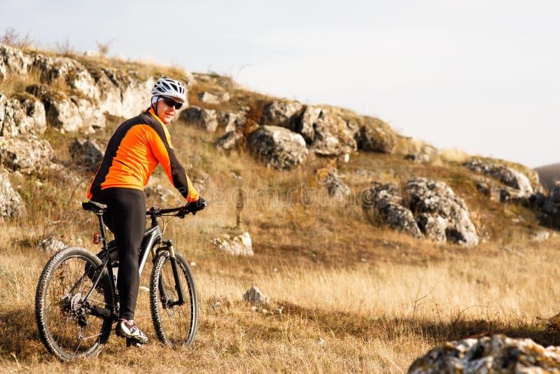 Radfahrer in der orange Jacke, die das Fahrrad auf Rocky Trail reitet Extremes Sport-Konzept Raum für Text lizenzfreie stockbilder