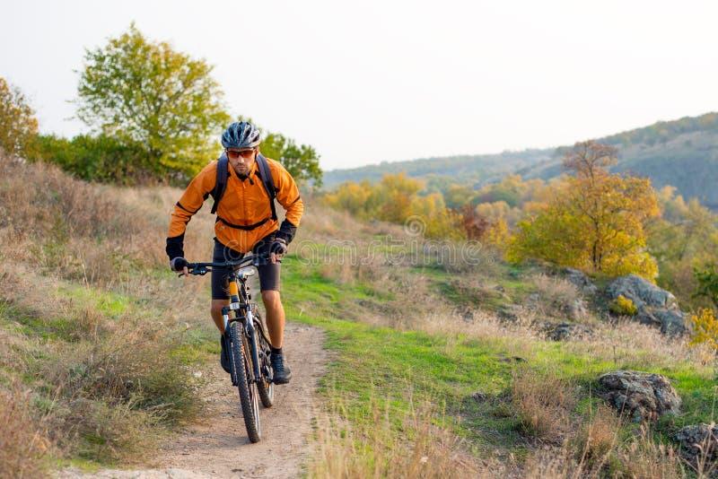 Radfahrer in der Orange, welche die Mountainbike auf Autumn Rocky Trail reitet Extremer Sport und radfahrendes Konzept Enduro stockfoto