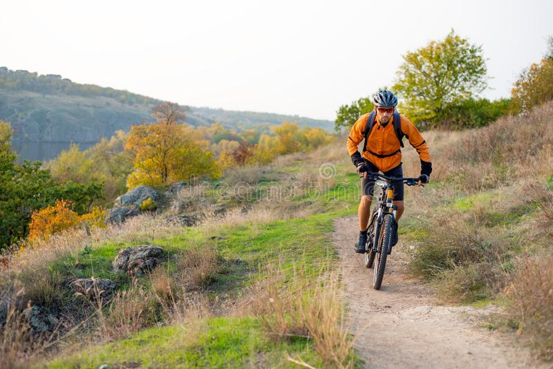 Radfahrer in der Orange, welche die Mountainbike auf Autumn Rocky Trail reitet Extremer Sport und radfahrendes Konzept Enduro stockbilder