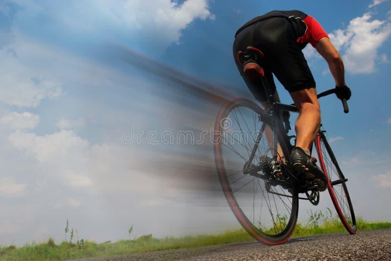 Radfahrer, der schnell auf die Asphaltstraße fährt stockbilder