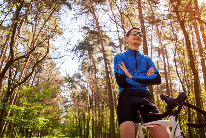 Radfahrer des jungen Mannes, der im Fr?hjahr einen Mann Wald des Rennrads hat Rest reitet stockfoto