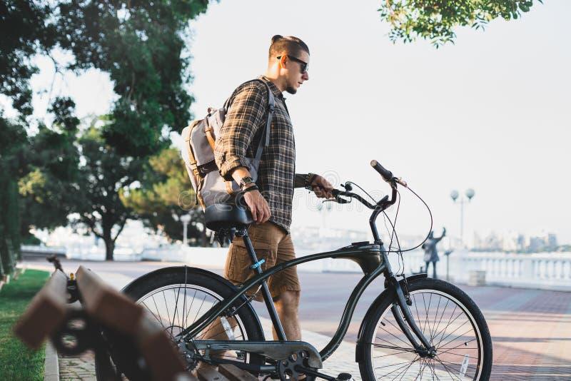 Radfahrer des jungen Mannes geht mit Fahrrädern auf Damm Sommer im täglicher Lebensstil-städtischen stillstehenden Konzept lizenzfreie stockfotografie