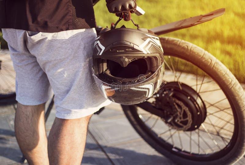 Radfahrer des jungen Mannes mit dem Schutzhelm in der Hand, der nahe elektrischem Fahrrad steht lizenzfreie stockbilder