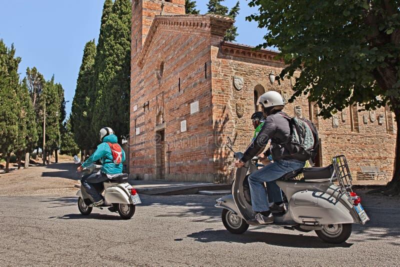 Radfahrer, die Weinleseroller Vespa reiten stockbild