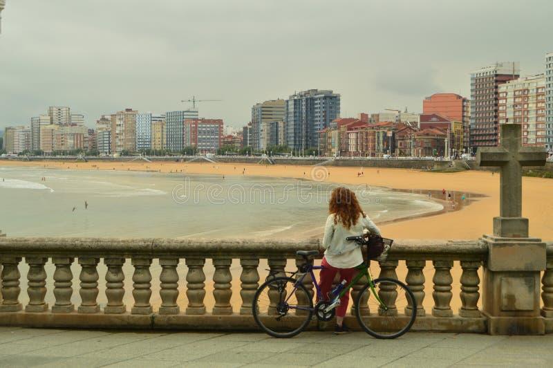 Radfahrer-Frau, welche die Ansichten der Bucht mit einem Kreuz neben ihr auf dem Strand von San Lorenzo In Gijon genießt Reise, F lizenzfreie stockfotos