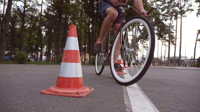 Radfahrer gehen ringsum Verkehrskegel Junger gutaussehender Mann, der Weinlesefahrrad fährt Sportlicher Kerl, der am Park radfähr lizenzfreie stockfotografie