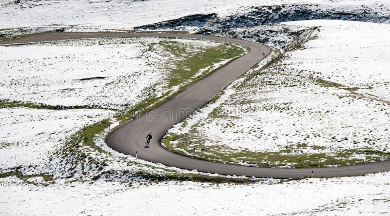 Radfahrer geht abwärts eine Gebirgsstraße in einer schneebedeckten Landschaft entlang stockfotos