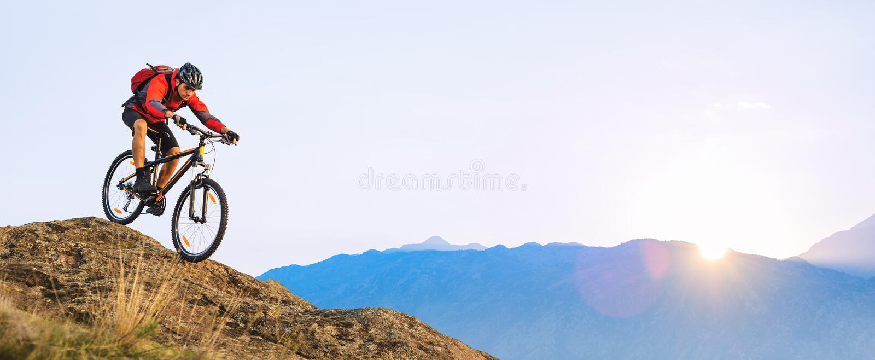 Radfahrer im roten Reiten das Fahrrad hinunter den Felsen bei Sonnenaufgang Extremer Sport und radfahrendes Konzept Enduro stockfoto