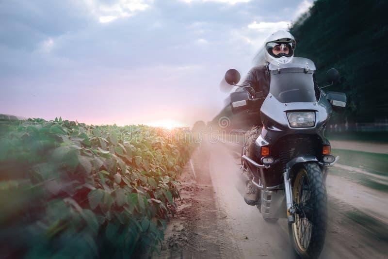 Radfahrer-Mann-Reiten auf Abenteuer-Motorrad, Sommersonnenuntergang, Sonnenaufgang, weg vom Straßenreisekonzept, weg enduro Reit stockfotografie