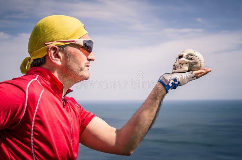 Radfahrer mit Bandana Stirnband, das einen Schädel betrachtet stockfotografie