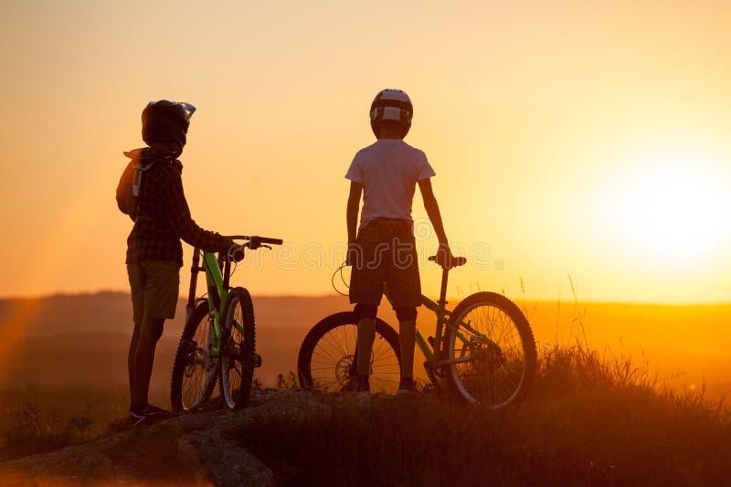 Radfahrer mit Mountainbiken auf dem Hügel am Abend lizenzfreie stockfotos