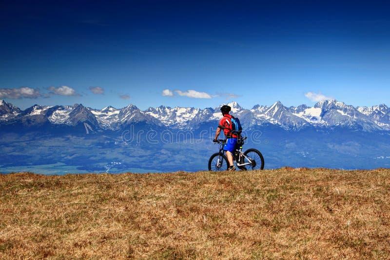 Radfahrer reitet eine Mountainbike vor schneebedeckten Tatra-Spitzen Slowakei lizenzfreies stockfoto