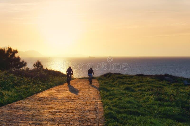 Radfahrer silhouettiert Reiten auf Park nahe dem Meer lizenzfreie stockfotos
