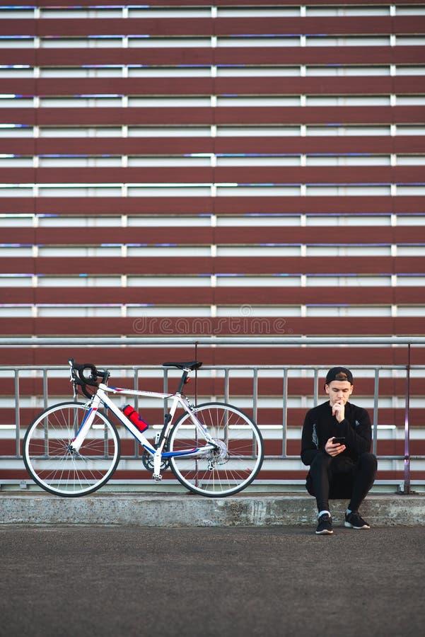 Radfahrer sitzt auf dem Hintergrund der Wand und benutzt einen Smartphone Copyspace stockfotos