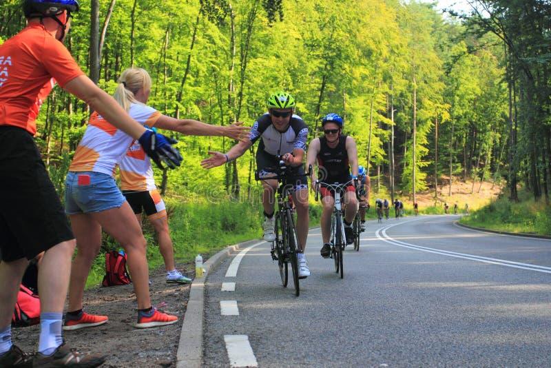 Radfahrer während eines Rennens auf dem Triathlonweg, der durch Fans sich stützt lizenzfreie stockfotografie