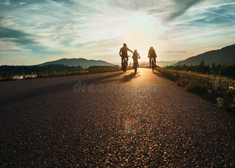 Radfahrerfamilie, die auf die Straße bei Sonnenuntergang reist lizenzfreie stockfotografie
