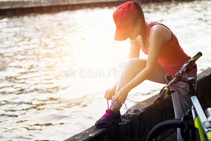 Radfahrerfrau, die shoeslace entlang dem Kanal im Sonnenuntergang bindet stockbilder