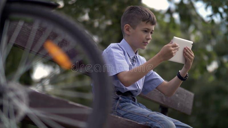 Radfahrerjunge, der auf Bank im Park nach dem Reiten der Fahrradgebrauchstablette sitzt lizenzfreie stockfotografie
