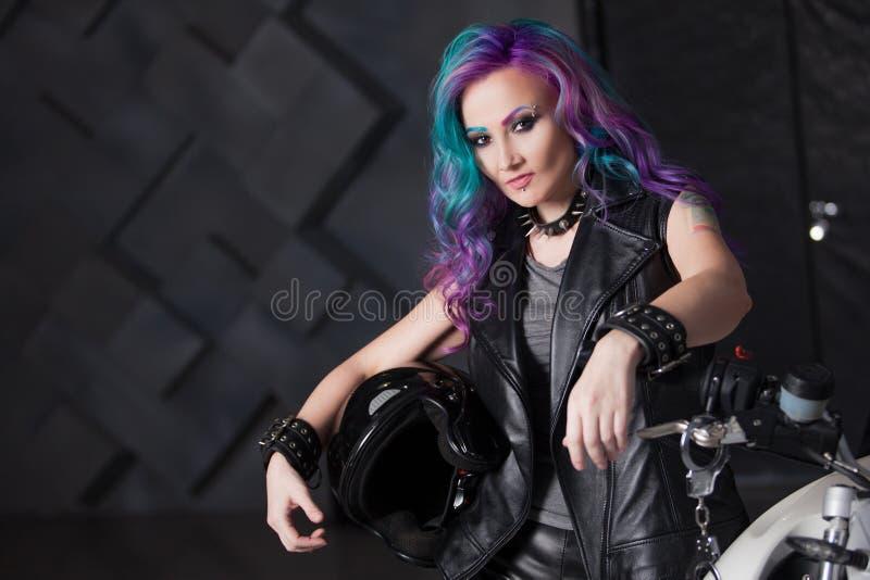Radfahrerk?ken vor Motorrad Sch?ne und PERT junge Frau in der ledernen Kleidung stockbild
