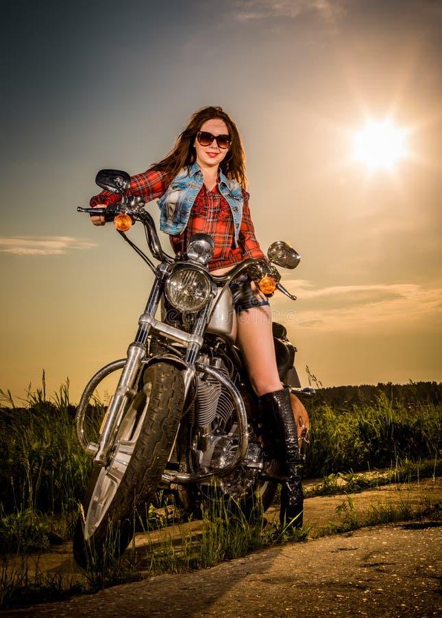 Radfahrermädchen, das auf Motorrad sitzt stockfoto