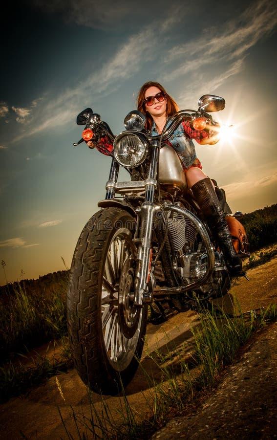 Radfahrermädchen, das auf Motorrad sitzt lizenzfreie stockfotos
