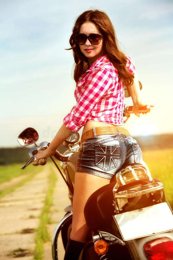 Radfahrermädchen, das auf Motorrad sitzt lizenzfreies stockfoto