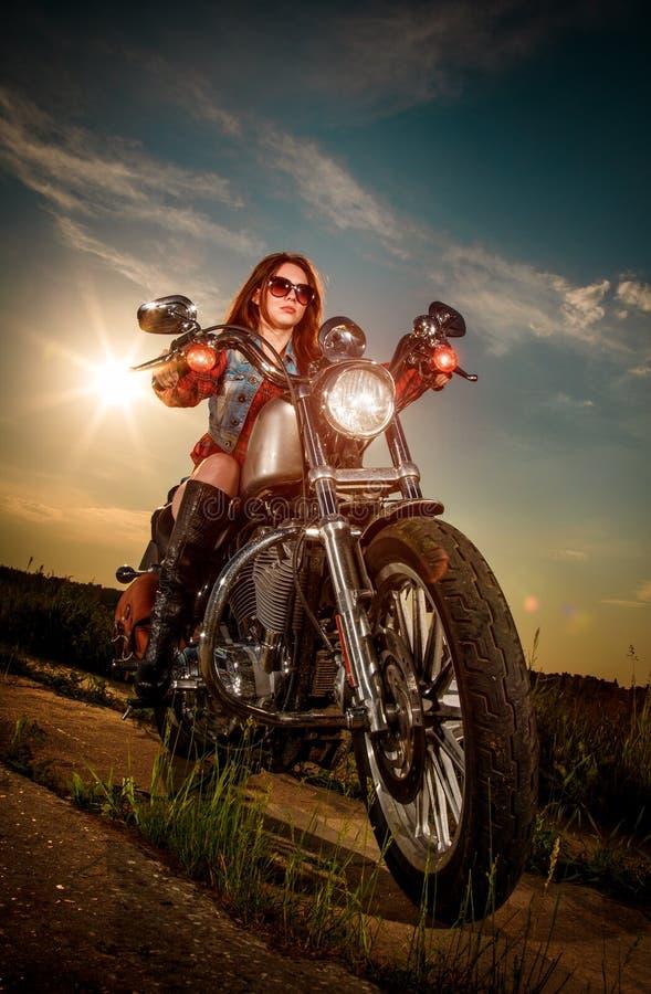 Radfahrermädchen, das auf Motorrad sitzt stockfotos