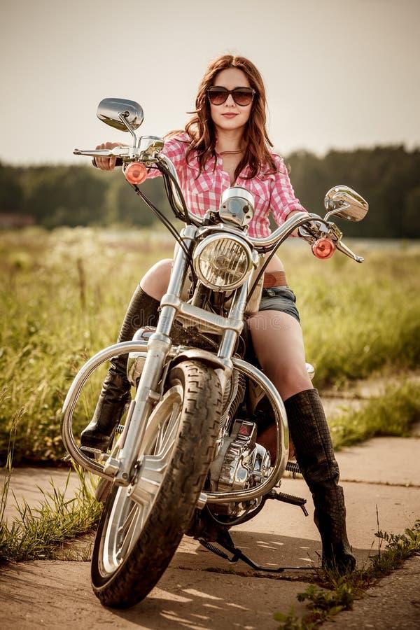 Radfahrermädchen, das auf Motorrad sitzt lizenzfreie stockbilder