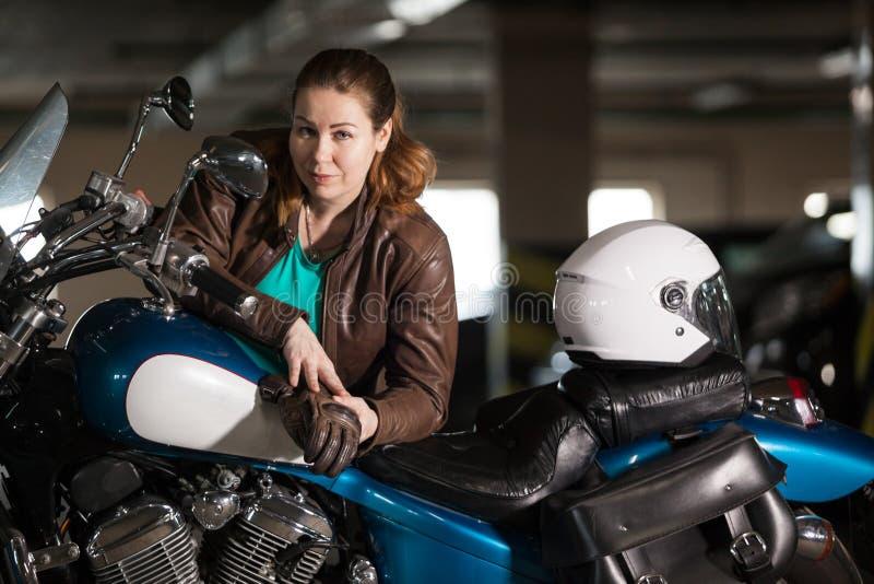 Radfahrermädchen in der Lederjacke, die auf Motorrad im Parkplatz, im blauen Motorrad und im weißen Sturzhelm aufwirft lizenzfreies stockfoto