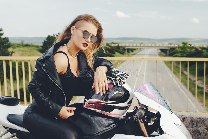 Radfahrermädchen in einem Leder kleidet auf einem Motorrad stockbilder