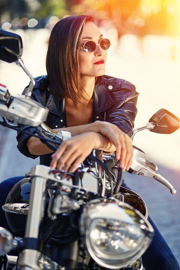 Radfahrermädchen in einer Lederjacke auf einem Motorrad stockfoto