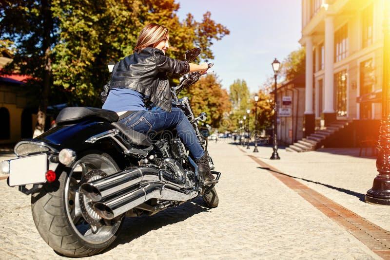 Radfahrermädchen in einer Lederjacke auf einem Motorrad lizenzfreies stockfoto