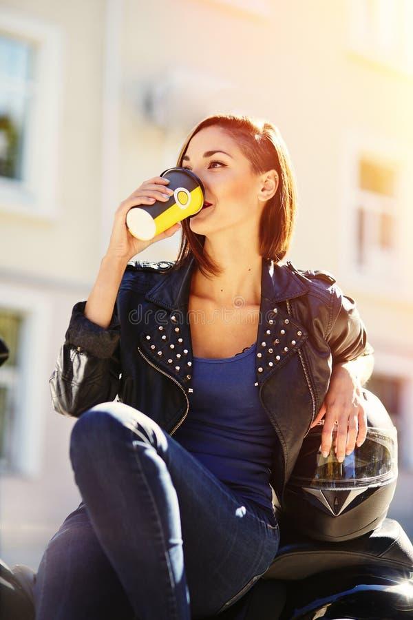 Radfahrermädchen in einer Lederjacke auf einem trinkenden Kaffee des Motorrades lizenzfreies stockbild