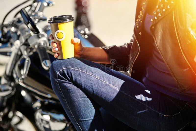 Radfahrermädchen in einer Lederjacke auf einem trinkenden Kaffee des Motorrades lizenzfreie stockfotos