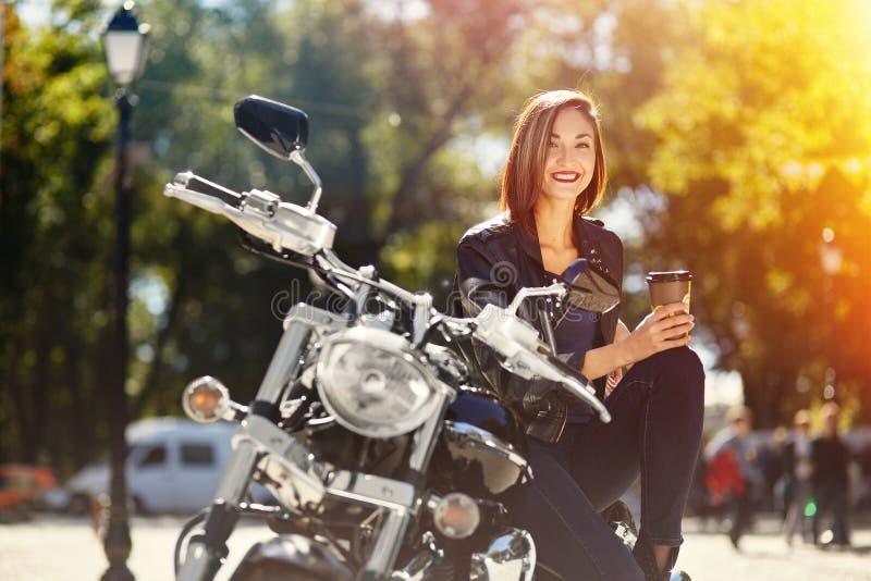 Radfahrermädchen in einer Lederjacke auf einem trinkenden Kaffee des Motorrades stockbilder