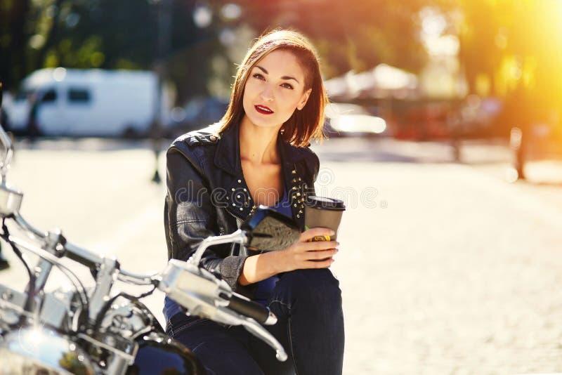 Radfahrermädchen in einer Lederjacke auf einem trinkenden Kaffee des Motorrades lizenzfreie stockbilder