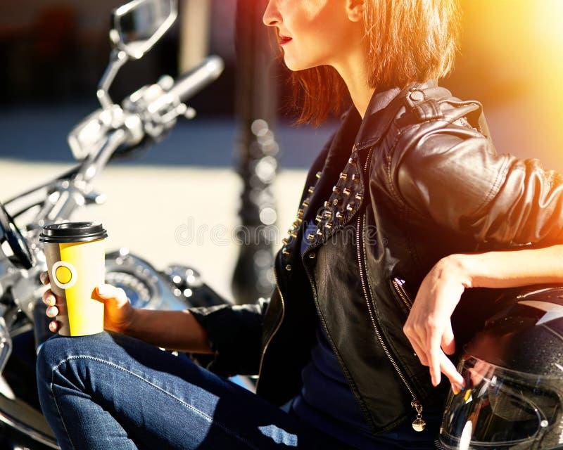 Radfahrermädchen in einer Lederjacke auf einem trinkenden Kaffee des Motorrades lizenzfreies stockfoto