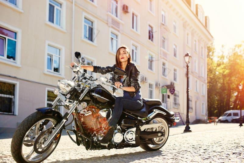 Radfahrermädchen in einer Lederjacke, die ein Motorrad reitet lizenzfreie stockbilder