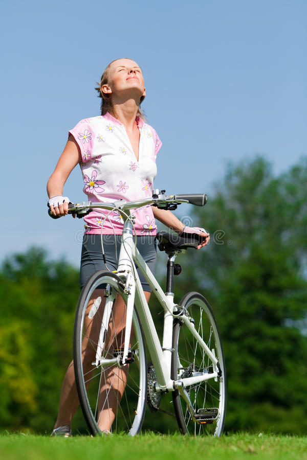 Radfahrermädchen, welches die Sonne enjoing ist stockfotos