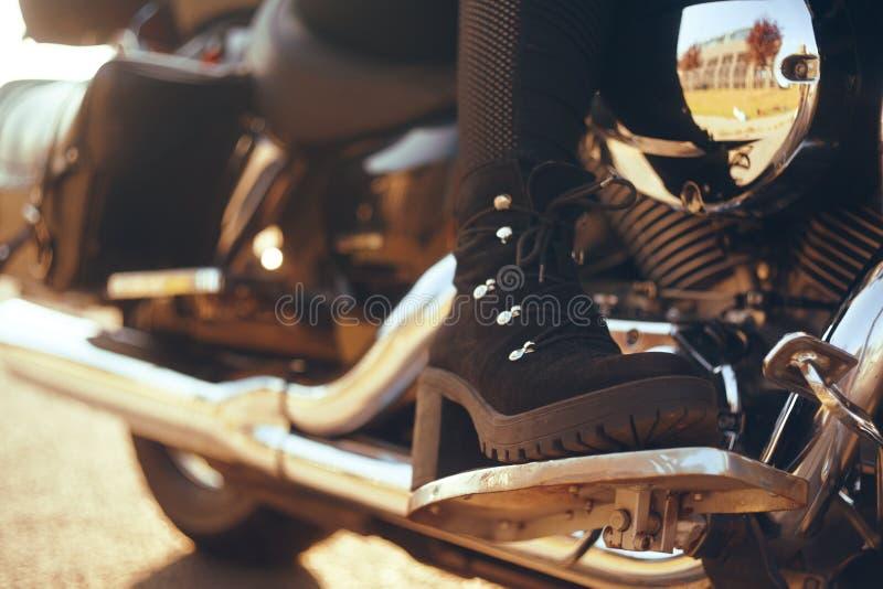 Radfahrerm?dchenreiten auf einem Motorrad Ansicht von unten der Beine in den Lederstiefeln Beinmädchen mit Fersen auf einem Fahrr stockbild