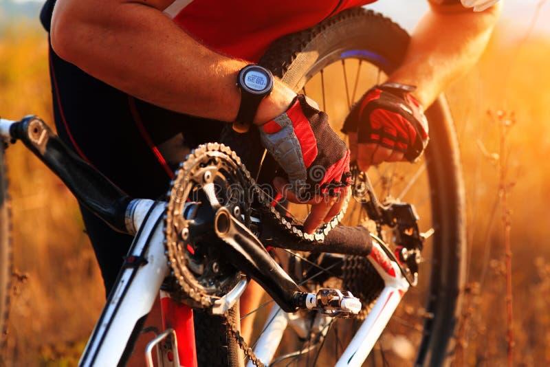 Radfahrermann, der seine Mountainbike in der sonnigen Wiese repariert lizenzfreie stockfotos