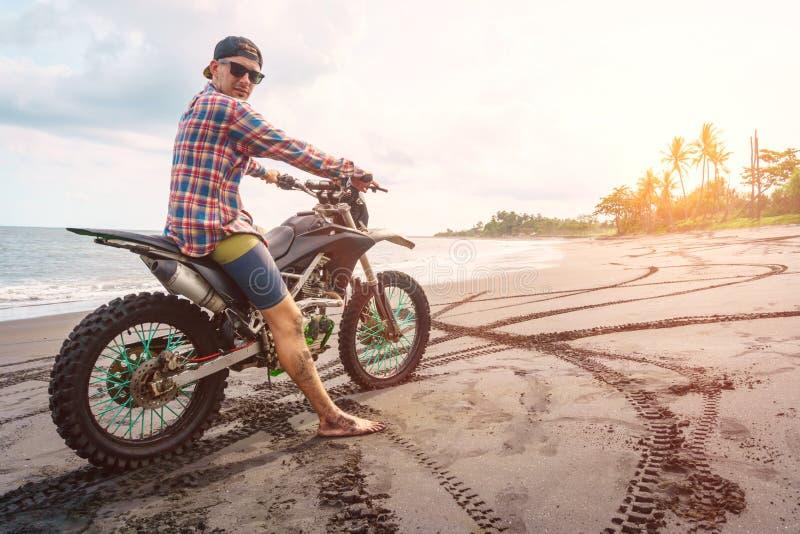Radfahrermann mit seinem Sportmotorrad auf schwarzem Sandstrand stockfoto