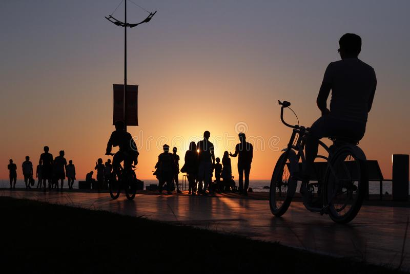 Radfahrerschattenbild auf Seestrand gedrängtem Sonnenunterganghintergrund stockbild