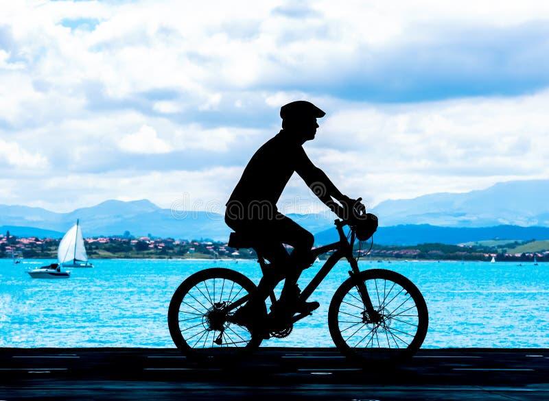 Radfahrerschattenbild nahe dem Meer am sonnigen Tag lizenzfreie stockfotografie