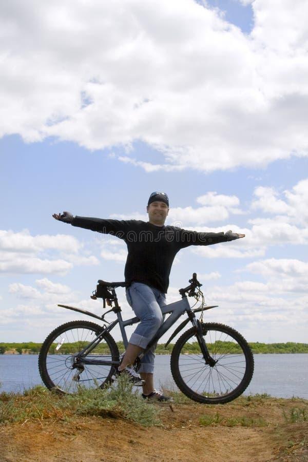 Radfahrerstellung über großem Wolkenhimmel stockbild