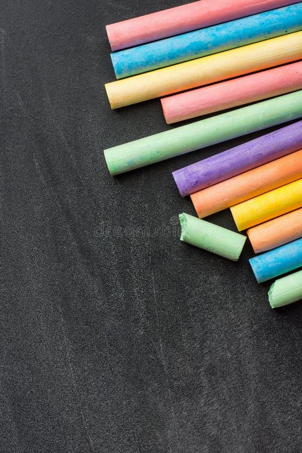 Radhög av mångfärgade Chalksfärgpennor på den mörker skrapade svart tavla Dra tillbaka till den grafiska designen för skolaaffärs royaltyfria bilder