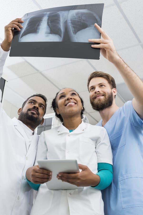 Radiólogos de sexo masculino y de sexo femenino que examinan la radiografía del pecho en hospital fotos de archivo libres de regalías