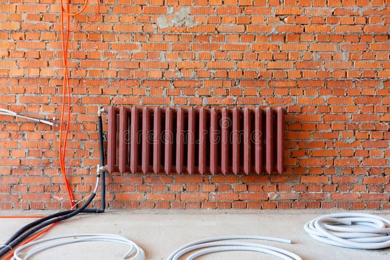 Radiador e pacotes de tubulações onduladas contra uma parede de tijolo Interior durante o reparo foto de stock royalty free