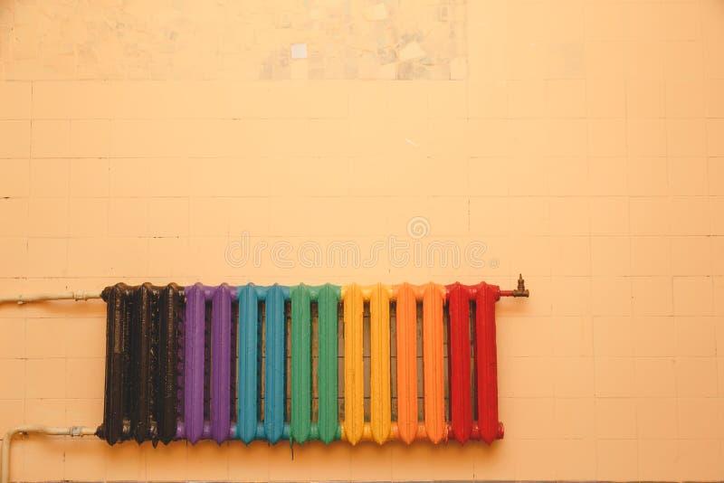 Radiador viejo del arrabio, pintado en diversos colores en una pared en blanco foto de archivo