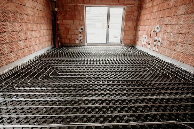Radiant floor construction installation with flexible pipes. Installation of underfloor heating stock images